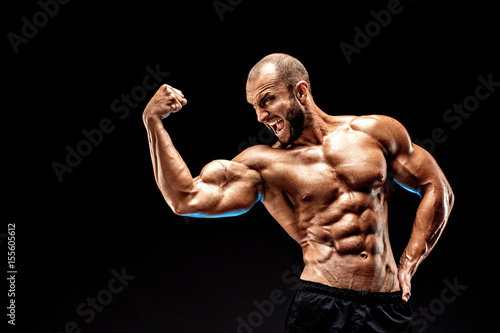 Strong bodybuilder man with perfect abs, shoulders,biceps, triceps and chest showing his biceps. Scream motivation.