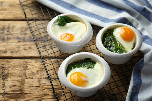 Fotomural Bowls with eggs and spinach on wooden table
