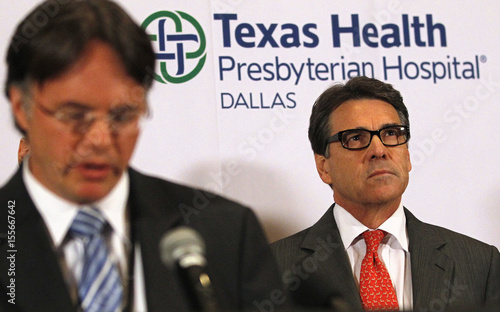 Texas Governor Perry listens as Lakey, M D  Commissioner, Texas
