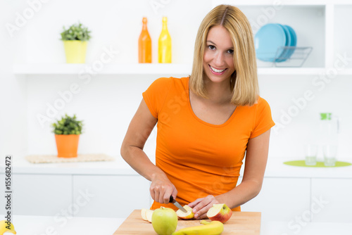 Plakat Ładna kobieta tnie owoce