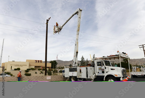 Workers with United Power Contractors install a power pole