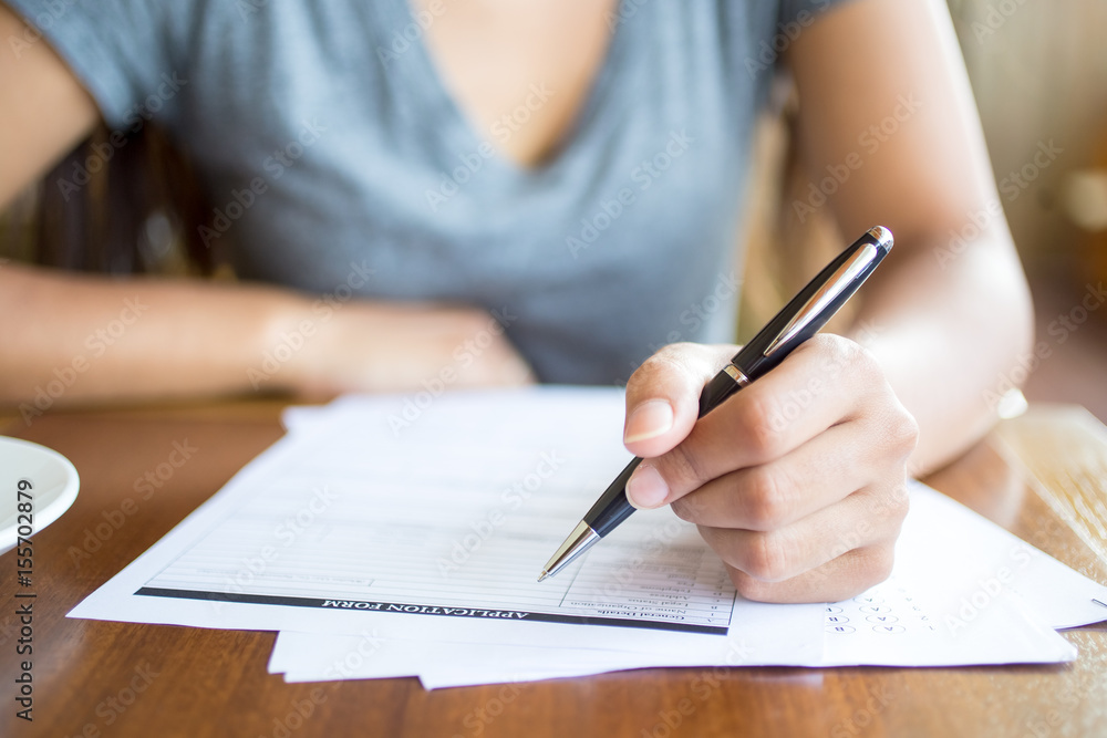 Fototapeta Close-up of woman filling application form