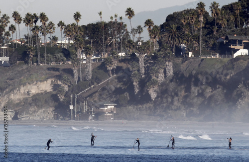 Paddle boarders gather during a warm weather spell off the