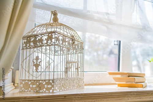 Fotografia  Close up decorative birdcage on windowsill