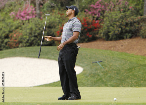 Woods reacts to missing an eagle putt on the 13th hole during first ...