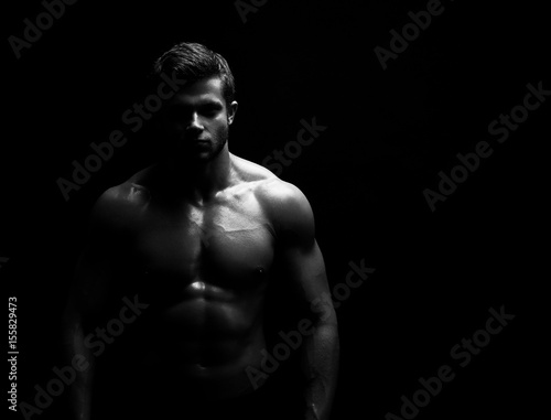 Black and white studio shot of a strong unrecognizable young handsome male athlete posing shirtless on black background copyspace bodybuilder man with muscular body fitness sports willpower concept.