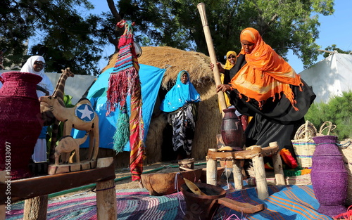 A Somali woman displays traditional items and prepares food