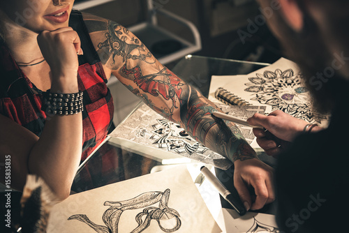 Photo Female hand with tattoo situating on desk