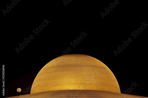 The Full Moon Is Seen Over The Buddhist Wat Phra Dhammakaya Temple