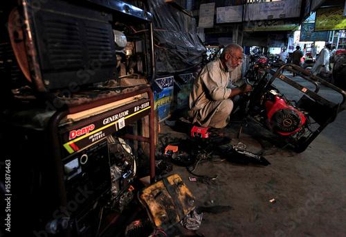 a generator mechanic works outside his shop in rawalpindi