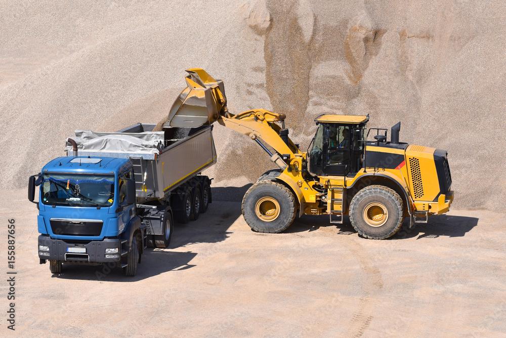 Beladung LKW durch Radlader in einem Kieswerk mit Baustoff Sand ...