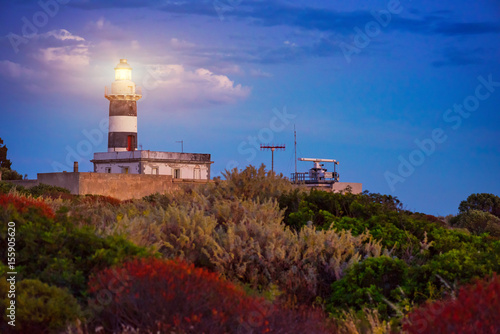 Lighthouse at sunset surrounded in the Mediterranean vegetation composed of multicolored bushes