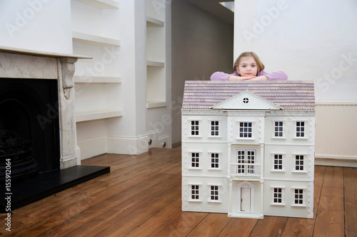 Photo  A girl resting on her dollhouse.