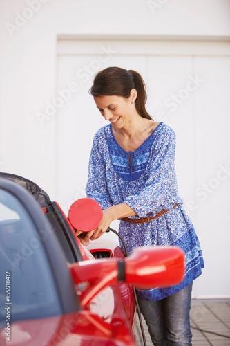 Fotografie, Obraz  Woman plugging in her electric car