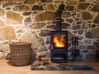 The interior of a cosy, stone cottage with stone walls and a fireplace with logs burning in a wood burner on a fireplace and hearth.
