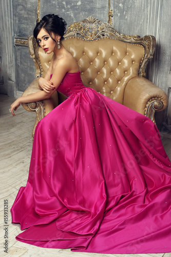 Elegant Srunning Woman Sitting In Armchair And Looking At You
