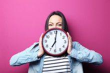 Young Woman Holding A Clock On...