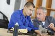 Apprentice receiving advice from senior engineer