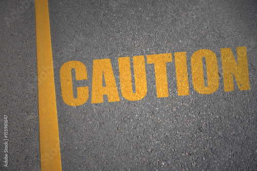 Fotografering  asphalt road with text caution near yellow line