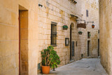 Fototapeta Uliczki - Narrow street of Silent City with a small restaurant, Mdina, Malta