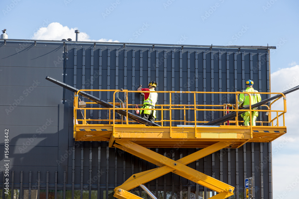 Fototapety, obrazy: Workers on the aerial work platform at facade installation work