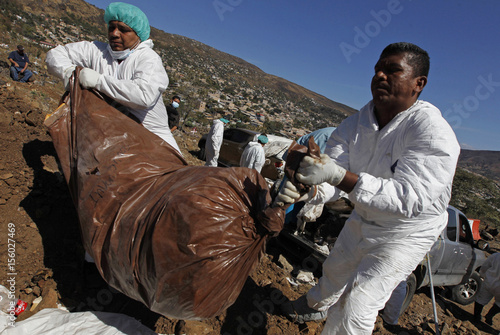 Morgue workers carry a bag containing an unidentified body into a