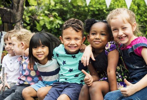 Photo Group of kindergarten kids friends arm around sitting and smiling fun