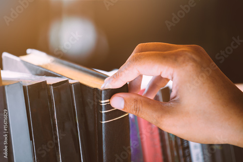 Fototapety, obrazy: Woman hand finding and selecting a book on bookshelf in the library in vintage color tone