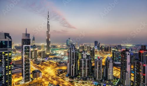 Fototapeta Fantastyczny widok z lotu ptaka Dubaju, ZEA, o zachodzie słońca. Futurystyczna architektura wielkiego nowoczesnego miasta w dramatycznym świetle. Kolorowa nocna linia horyzontu. Tło podróży.