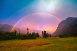 Fototapeta Tęcza - Beautiful rainbow over the mountains during sunset. Wilderness Norway