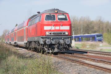 Roter Triebwagen zieht Eisenbahnwaggon