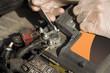 Dłonie mechanika samochodowego w rękawiczkach jednorazowych odkręcają klemę akumulatora. Klema akumulatora odkręcana przez serwisanta. Naprawa samochodu w warsztacie. Odłączanie akumulatora.