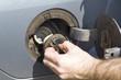 Mężczyzna odkręca korek wlewu paliwa w samochodzie. Męska dłoń otwiera wlew paliwa w samochodzie