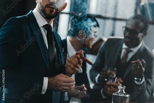 Fototapeta businessman smoking cigar with multicultural business team spending time behind obraz