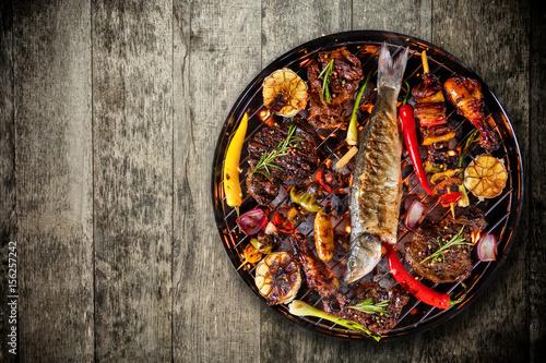 Plakat Odgórny widok świeży mięso i warzywo na grillu umieszczającym na drewnianej podłoga