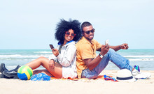 Happy Afro American Couple Using Mobile Phone Back To Back On The Beach