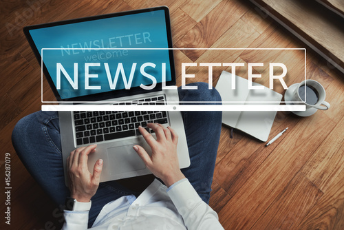 Fototapeta Top view of young woman sitting on the wooden floor with laptop and coffee with newsletter inscription in the foreground obraz