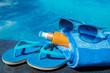 Sunglasses sunscreen cream blue slippers towel