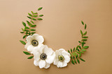 Anemone flowers wreath with green branches. Top view. Neutral background