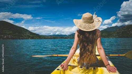 Young woman with hat and beautiful long hair relaxing in kayak on alpine lake