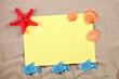 Starfish and seashells lying on the sand on the postcard.