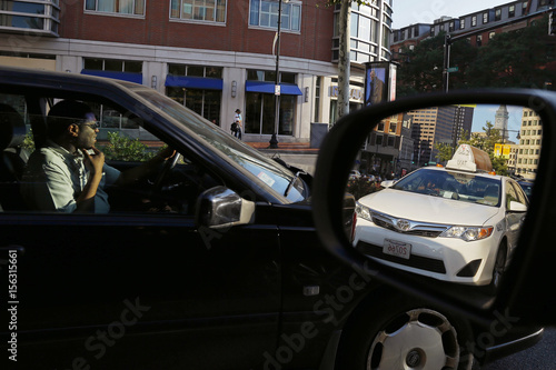 A taxi is reflected in the rear view window of a car sitting