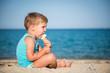 Sweet little child eating ice cream on beach, summertime
