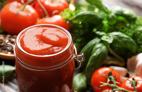 Fotografía  Composition of ketchup in jar and ingredients on wooden background