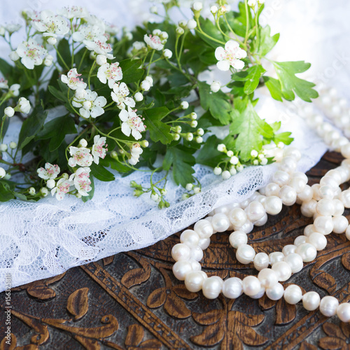 Fotografie, Obraz  Hawthorn blossom with lace and pearls on carved wood table