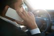 Businessman using phone in a car