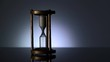 Wide shot of vintage metal hourglass turning over by male hand against gray background.