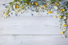 Spring Flowers Of Lilies Of The Valley, Forget Me Not, Daisies On A Wooden Background