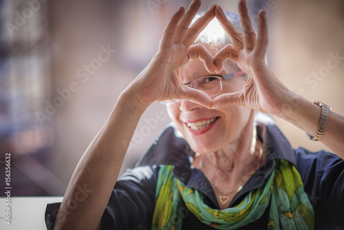 Fotografía  Cute senior old woman making a heart shape with her hands and fingers