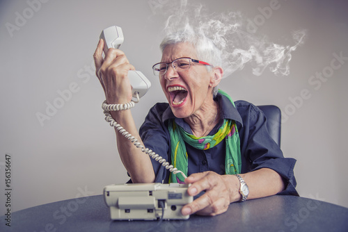 Fotografija  Angry, enraged senior woman yelling at a landline office phone, unhappy with cus